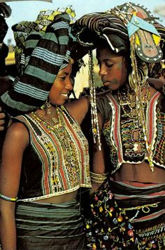 "Africa | Young wodaabe girls attending a Geerewol festival.  As a final decorative touch, a young girl integrates new sandals to her headdress | Page 504, National Geographic October 1983, 'Niger's Wodaabe:""People of the Taboo""; article and photos by Carol Beckwith."