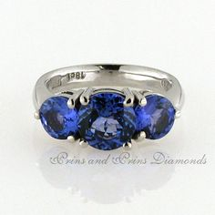 The centre stone is a 1.81ct bV round cut tanzanite with 2 = 1.50ct (6mm) round cut tanzanite gemstones set in an 18k white gold trilogy setting