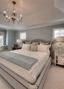 Master Bedroom Features Built In Window Seat And Tray Ceiling With Glass  Chandelier Over Bed.