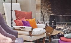 brightly colored pillows on nuetral chair