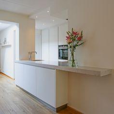 Door het composieten blad en het gebruik van lichte natuurlijke kleuren is deze keuken een verlengde van de woonkamer. #keuken #composiet #werkblad #ruimte #ruimtelijk #design #interieur #inspiratie