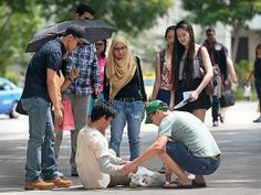 Do a good deed, you're on candid camera: Engineer Poh Jing Chieh (with green cap) and head of business development Samsul Ariffin (far left) helping Ziyad Bagharib, 21, after he fell while posing as a beggar for the Hidden Good project. http://www.straitstimes.com/news/singapore/more-singapore-stories/story/do-good-deed-youre-candid-camera-20140518 Photo: Ng Sor Luan/The Straits Times