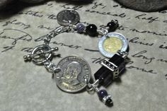 Kenya 1 Schilling, Mexico 1 Estados, UK 5 Pence coin bracelet with square purple glass, round amethyst and round black jasper beads.  Silver plate findings and toggle clasp.