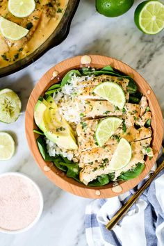 This Paleo and Whole30 friendly coconut lime chicken is so flavorful, fresh and satisfying! Coconut lime chicken in a bowl with spinach, rice, avocado and lime wedges and cilantro on top.