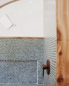 Shower details in Siya & Kristen's new Airstream home. Built-in shelving, plexiglass divider (peeking into the bedroom), copper fixtures, blue penny tile, and cedar framing. Our favorite element!