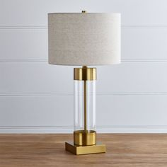 Shop Avenue Brass Table Lamp with USB Port.  An illuminating mix of modern and metal, our grandly scaled table lamp caps off its tall, cylindrical clear glass base with warm brass accents.  A linen drum shade adds textural counterpoint.