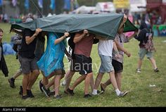 Glastonbury, Somerset, UK. 26th June, 2014. Festival goers cover up from the rain at the 2014 #Glastonbury festival © Lloyd/Alamy Live News