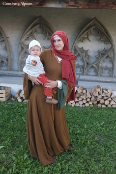 Woman wearing a bliaut, with child. Comthurey Alpinum, 12th century Medieval Reenactment 1180 ad.
