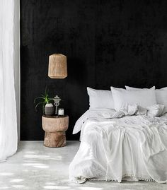 Black wall in an all white bedroom