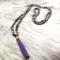 """Gray beaded necklace with purple leather tassel Beautiful handmade gray bean beaded necklace purchased in Peru with purple leather tassel. 25"""" in drop length on necklace with 3"""" leather tassel. Can be layered or double wrapped for your personalized look. Each of the beads is unique and different shades of gray. Jewelry Necklaces"""