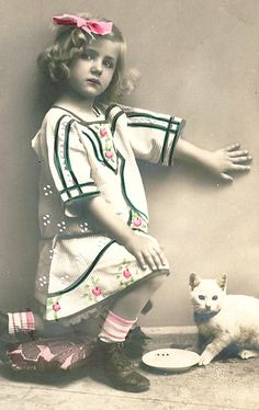 Vintage postcard featuring a photograph of a girl and a cat.
