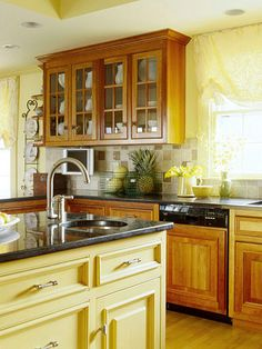 Traditional cabinets painted a soft yellow stand out against wood cabinetry. The dark countertop material ties the two tones together.