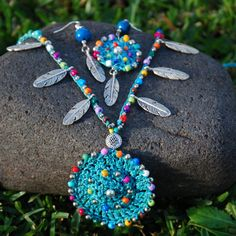 This beautiful necklace was crocheted with turquoise waxed cord, glass beads, metal beads and tibetan silver feathers. It can be worn close to the neck or more loose, you just tight it however you like it. The lace is long enough to wrap it 2 times around the neck. Each end of the