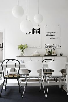 black and white dining space with mismatched chairs and posters hung with bulldog clips (photo by Frida Ramstedt)