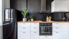 Yksiön pieni keittiö on remontoitu tyylikkäästi mustavalkoiseen värimaailmaan. Keittiön välitila ja seinä on maalattu mattamustalla, mikä tuo kivasti kontrastia vaaleisiin kaapistoihin. Musta Smeg-jääkaappi istuu keittiöön kuin nenä päähän!