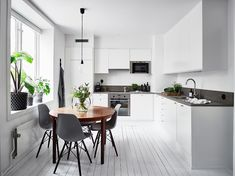 White kitchen with a round dining table - COCO LAPINE DESIGNCOCO LAPINE DESIGN