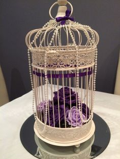 Cadburys purple bird cage centrepiece with roses and pearls. Bespoke Welsh wedding centrepieces from www.affinityeventdecorators.com