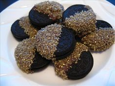 chocolate dipped oreo cookies gold sprinkles on a white plate