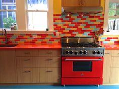 Final product. Looks like the photo collage I made!! Orange Silestone counter. Clayhaus tile. Vertical grain doug fir cabinetry. Laguna blue marmoleum floor. Traffic red Bluestar range.
