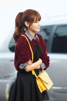 Welcome back! The preppy look is not new; it's classic, never really goes out of style. Choi Sooyoung of Girls' Generation was spotted at an airport wearing this outfit, made a little more modern by a navy blue skater skirt and bright yellow bag. For more on this trend see Asian Street Fashion: The Preppy Varsity Look in DF News! www.dramafever.com/news/ - Lily