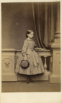 """portrait of a young girl standing by a balustrade and holding a hat, photographed by """"Merrick"""" at Joseph Langridge's photographic studio, 33 Western Road, Brighton (c1864)"""
