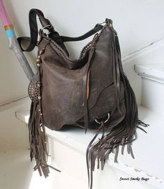 *New leather hobo bag - Fully handmade, artistic piece made by Sweet Smoke Bags * Made of natural brown Italian distressed leather, strong and soft , really nice quality * 3D front pocket, really roomy, perfect for smartphone * Lined with cotton fabric * 2 Interior pockets *Metal zip top closure * Handmade fringes * Back pocket * Decorative back charm *Dimensions: 15,5H / 15,5W, Strap adjustable - end of the strap was left unattached for regulation and then tied on <------ONE OF A KIN...