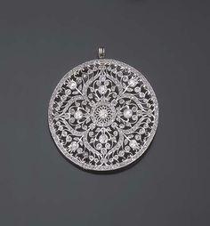 PENDENTIF BELLE EPOQUE DIAMANTS De forme circulaire entièrement repercé d'un décor floral pavé de petits diamants taillés en roses, le centre orné d'un motif quatre-feuilles sertis de diamants taille ancienne plus importants, monture en platine, vers 1910