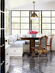 black arabesque tiles in shiny finish reflects light keeping the room from seeming too dark, wooden  chairs add a warm touch and white walls bring modern touch / bhg.com #kouboo