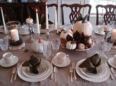 You can create a simple table centerpiece from painted pumpkins, freshly fallen leaves, pine cones and acorns. White tableware adds a sophisticated elegance and contrasts nicely with the French grey tablecloth. Earthy greens, browns, and reds tie the entire table together