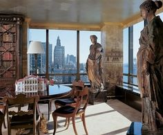 Nicholas Miles Pentecost Interiors - Thirty Rockefeller Plaza, New York City - Wallpaper, copied from antique panels, covers the walls of the dining room. Terra-cotta heroic figures stand sentinel over the round Regency table, which holds a Palladian model by Peter Kooz. William IV mahogany chairs from Florian Papp; Beauvais carpet.