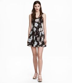 Black/floral. Short, sleeveless dress in thick jersey. Low-cut neckline at back, seam at waist, and flared skirt.