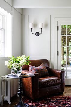 Beautiful reading nook with leather chair, small end table, and wall mounted sconce