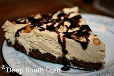 A pie made of peanut butter, cream cheese, cream and brown sugar, prepared in a chocolate cookie crust and garnished with chocolate syrup and chopped peanuts.