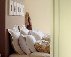 Pour une chambre calme, pensez au teintes naturelles et douces. Pour une ambiance reposante, cette chambre capitalise sur de chaudes nuances de crème et de brun sur les murs, qui font ressortir la parure de lit en voile de coton et les coussins matiérés.
