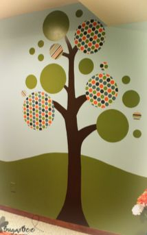 tree mural for a playroom - love this!  it has some painted circles and some fabric circles.  The tutorial even shows how to attach fabric easily to the wall