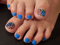 Pretty pedicure: bright flowers on the big toe nails, bright blue polish on the small toe nails