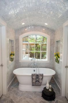The new master bathroom features this spectacular tub in an arched setting with tiled ceiling and recessed lighting. The arched shape of the space is echoed by the framing of the new window
