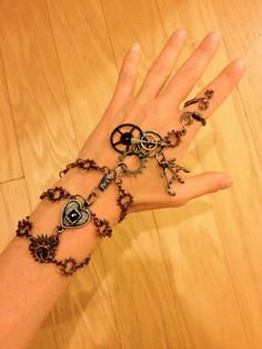 Lovely, one-of-a-kind ornamental piece perfect for a night out! Made from copper, brass, and Neo-Victorian charms. Adjustable to any finger/wrist size.  $35.00 plus shipping.  www.etsy.com/listing/188895200/steampunk-slave-bracelet