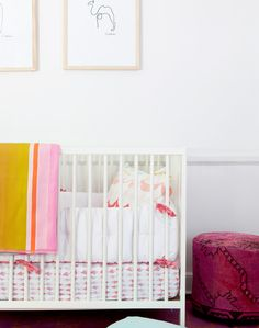 Colorful crib in white nursery
