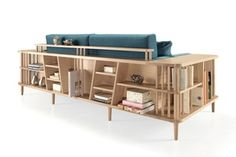 Scaffold sofa from Wewood is a sofa with surrounding wooden frame- place to sit, lay down, work, play, or store items.   Designed by André Teoman Studio, Scaffold is also a side table, a day bed, a bookshelf or a divider.   shelving units run alongside the armrests and the sofa's backrest. The frame is made from 100% solid wood structure, and the strong and minimalist lines are accentuated by the natural wood finish.