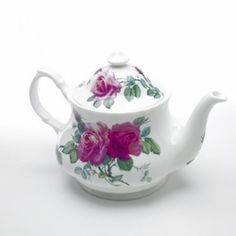 A Bold, yet Elegant Rose Pattern by Roy Kirkham, this bone china teapot is made in England.  Bold pink roses on a creamy white backgroung decorate the front and lid of this collectible teapot.    Matching Pieces Available  6 cup capacity