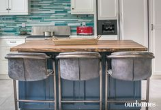 Steel and leather barstools provide convenient seating at the kitchen island. Teal coloured glass tiles serve as the kitchen backsplash.   http://www.ourhomes.ca/articles/build/article/whitewashed-weekender-ripe-with-rustic-chandeliers