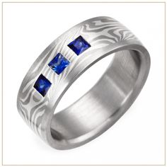 Ashes and Snow Mokume Gane Wedding Ring with Palladium Channel and Three Flush Set Sapphires. Andrew Nyce Designs offers this unique wedding band composed of stunning layers of 950 Palladium, Palladium 500, and Palladium-enhanced Sterling Silver set in a 950 Palladium channel with three 0.2 carat Princess cut Ceylon Blue Sapphires.