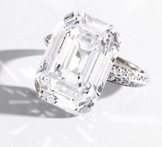 IMPORTANT PLATINUM AND DIAMOND RING The cut-cornered rectangular step-cut diamond weighing 9.77 carats, the mounting accented by small round diamonds weighing approximately .70 carat