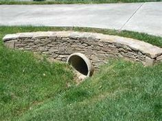 Stunning Private Culvert Landscaping Culvert Landscaping Retaining Wall Around Driveway Culvert Dry Stack Driveway Entrance Driveway Culvert, Driveway Entrance Landscaping, Landscaping Around House, Driveway Paving, Driveway Design, Concrete Driveways, Home Landscaping, Driveway Ideas, Rock Driveway