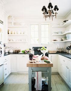 Kitchen with white walls, white shelves, white cabinets, black countertops, wood floors, and black and brass chandelier