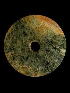 Jade disc, or Bi,  China, Neolithic period, Liangzhu culture, around 2500 BC. Stone rings were being made by the peoples of eastern China as early as the fifth millennium BC. Jade discs have been found carefully laid on the bodies of the dead in tombs of the Hongshan culture (about 3800-2700 BC), a practice which was continued by later Neolithic cultures. Large and heavy jade discs such as this example, appear to have been an innovation of the Liangzhu culture (about 3000-2000 BC).