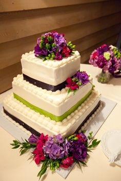 Purple and green themed wedding cake flowers created by Lexington Floral in Shoreview, Minnesota.    #weddingflowers #cakeflowers