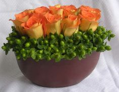 Green hypericum is wonderful with vibrant orange roses!