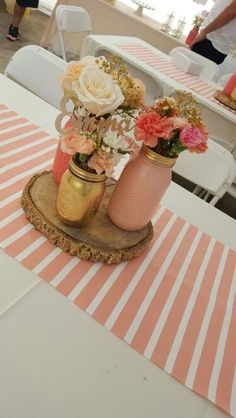 Baby shower Decor. centerpieces  mason jars painted with buttercream paint collection semi gloss coral,royal flush ,gold spray paint . Real wooden log - coaster . Glitter name purchased on etsy.  White ,peach and coral roses . White daisies.  Sprayed Glitter gold baby spread,pink and coral carnations . Striped coral table runner